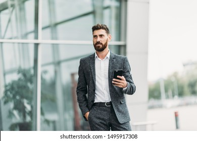 Businessman texting messages while walking