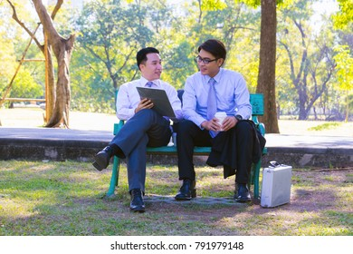 Businessman, They are sitting on bench in park. He is play notebook and  search internet. Another one holding a cup of coffee and talking about business in  relax time. Photo concept  business.