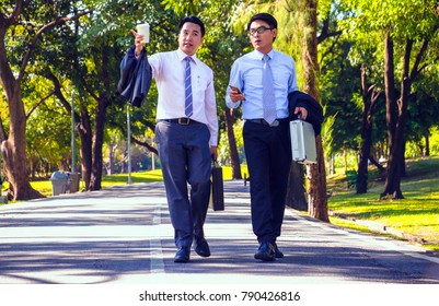 Businessman, They are walking on road in park. They are talking  business. He is drinking coffee and His friend holding business bag. Photo concept business and relax time.