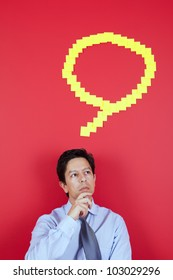 Businessman thinking next to a red wall
