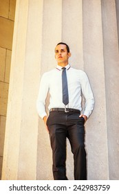 Businessman Thinking Outside. Dressing in a white shirt, a black tie, hands in pockets, a young handsome guy is standing outside a office building, lost in thought.