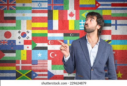 Businessman thinking over flags background