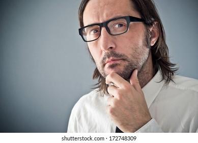 Businessman thinking, portrait with copy space. Adult unshaven businessman.