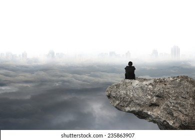 businessman thinking and sitting on cliff with gray cloudy sky cityscape background