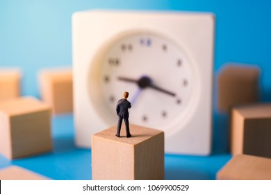 Businessman thoughtful with clock in background. Business concept of time.