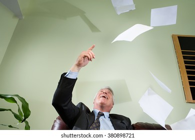 Businessman throwing paper in the air
