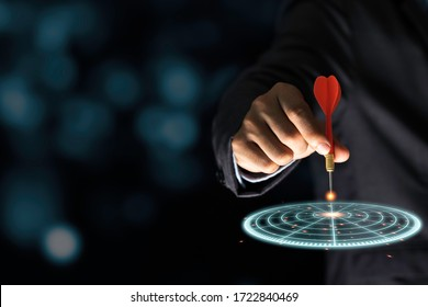 Businessman throwing red arrow dart to virtual target dart board. Setup objectives and target for business investment concept.