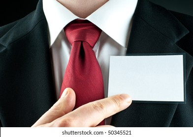 A businessman with a tie points on a blank name-tag