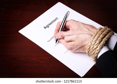 Businessman with tied hands signing an agreement document