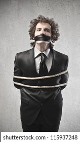 Businessman tied with a rope and gagged