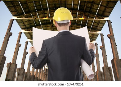 Businessman with time schedule under roof  building