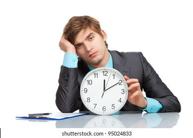 Businessman tired hold clock, sitting at the desk, handsome young business man bored looking at camera, wear elegant suit and tie isolated over white background