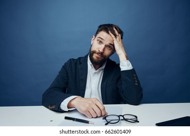 Businessman is tired, businessman is holding his head, business man on blue background.