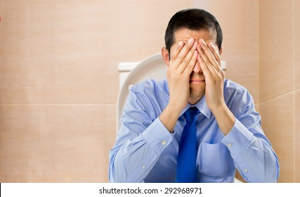 businessman in the toilet with problems of constipation