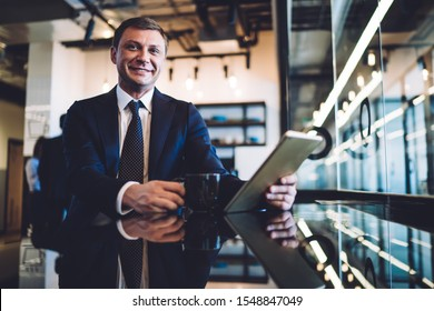 Businessman with toothy smile sitting at table next to window in contemporary design office while drinking tea and using tablet