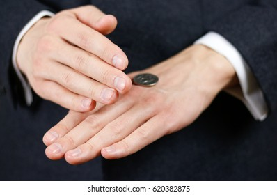 Businessman tossing a coin. Heads or tails. Close up.