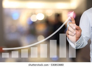 Businessman to touch in peak of Business graph on abstract blur background,Concept financial symbols coming success and profitability.