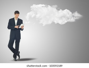 Businessman with touch screen Internet Tablet and the clouds