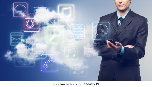 Businessman with touch screen phone and the cloud with applications icons on blue background