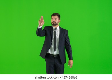 The businessman touch the virtual screen on the green background