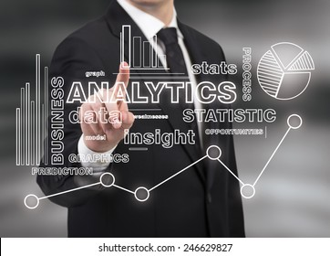 businessman touching analytics symbol on black background