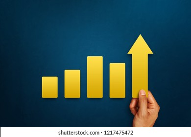Businessman is touching arrows pointing up with graph as a symbol of growth and success or rising successful development and business development in the future