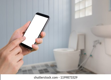 businessman touching blank screen on  smartphone, mobile, cell phone with blurry toilet room, concept of cleaning service.