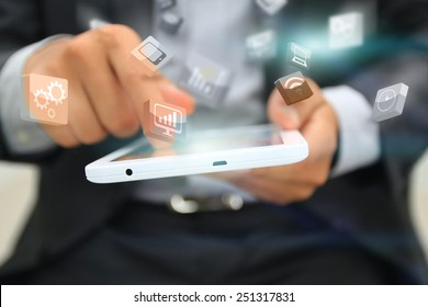 Businessman touching business icon on tablet.