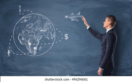 Businessman touching the drawn plane on the chalkboard with a globe. Recreation and tourism. Investing human and financial resources. Humanitarian assistance.