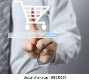 Businessman touching graphic of virtual shopping trolley icon at internet shopping application on social network website after search and select products, display on visual screen