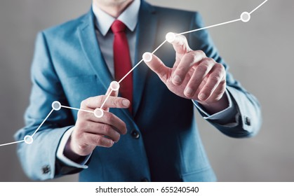 Businessman touching a growing graph