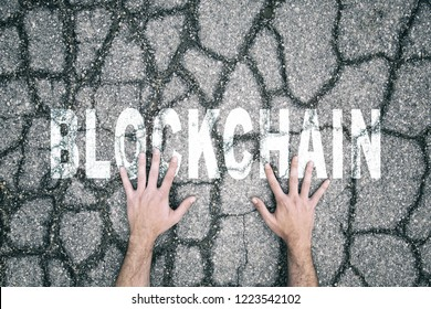 Businessman touching with his hands blockchain word painted on cracked and damaged asphalt floor.