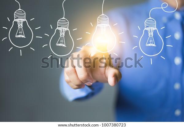 電球に触れ、革新的なテクノロジーと創造性を持つ新しいアイデアを持つ実業家。