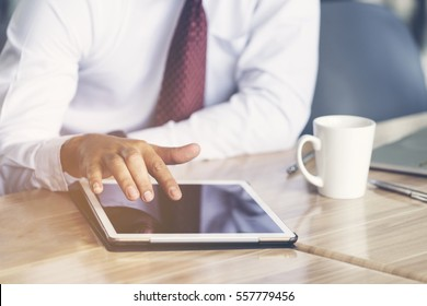 Businessman touching on digital tablet, searching website, playing social media and  checking stock exchange, sitting at coffee shop