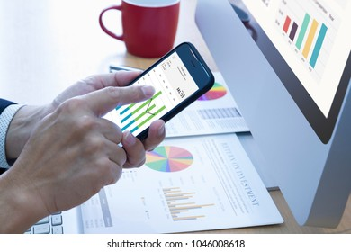 Businessman touching smart phone application screen in front of modern desktop computer analysing profit and loss or investment risk analysis.