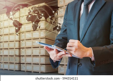 Businessman touching tablet for analyze stock at logistics port with blurred cargo warehouse background, transportation trading business concept, world map element of this image furnished by NASA