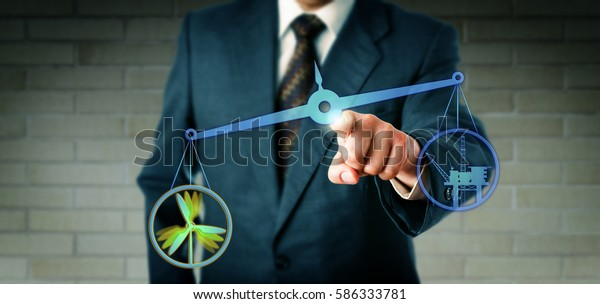 Businessman is touching a virtual pair of scales on which an offshore wind power icon is outweighing an oil an gas drilling rig symbol. Industry and technology concept for energy turn to renewable.