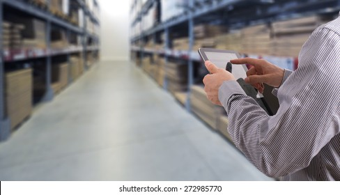 Businessman with touchscreen tablet checking inventory in stock room. Store house inspection