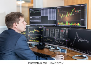 Businessman trading stocks. Stock traders looking at graphs, indexes, numbers and analyses on multiple computer screens in modern trading office.