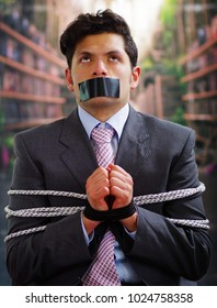 Businessman trapped in a chair with rope, with a black tape in his mouth and hands in a blurred background