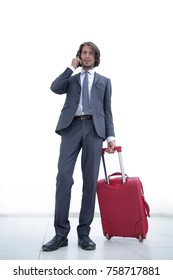 businessman with travel suitcase talking on mobile