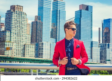 Businessman traveling, working in New York. Dressing in red blazer, blue collarless shirt, wearing sunglasses, a guy standing in business district with high buildings, confidently looking forward.