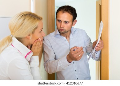Businessman trying to collect arrearages from housewife at doorway