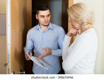 Businessman trying to collect money from mature housewife at home door. Focus on man