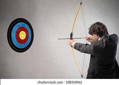 Businessman trying to hit a target with bow and arrow