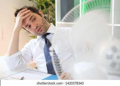Businessman trying to refresh at work in summer heat