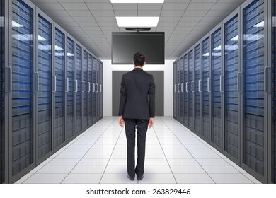 Businessman turning his back to camera against server hallway