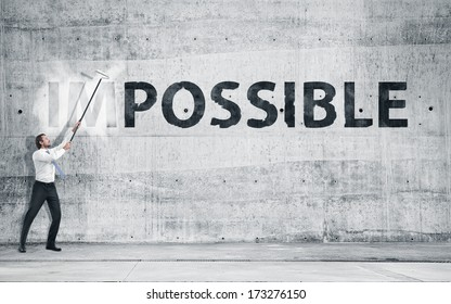 """Businessman turning the word """"Impossible"""" into """"Possible"""""""