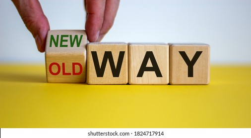 Businessman turns a cube and changes words 'old way' to 'new way'. Beautiful yellow table, white background. Copy space. Concept of new way choice.