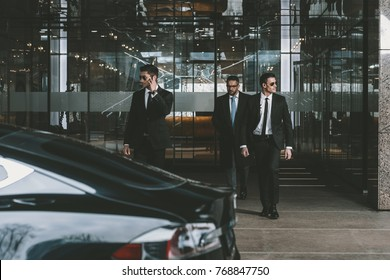 businessman and two bodyguards walking to auto